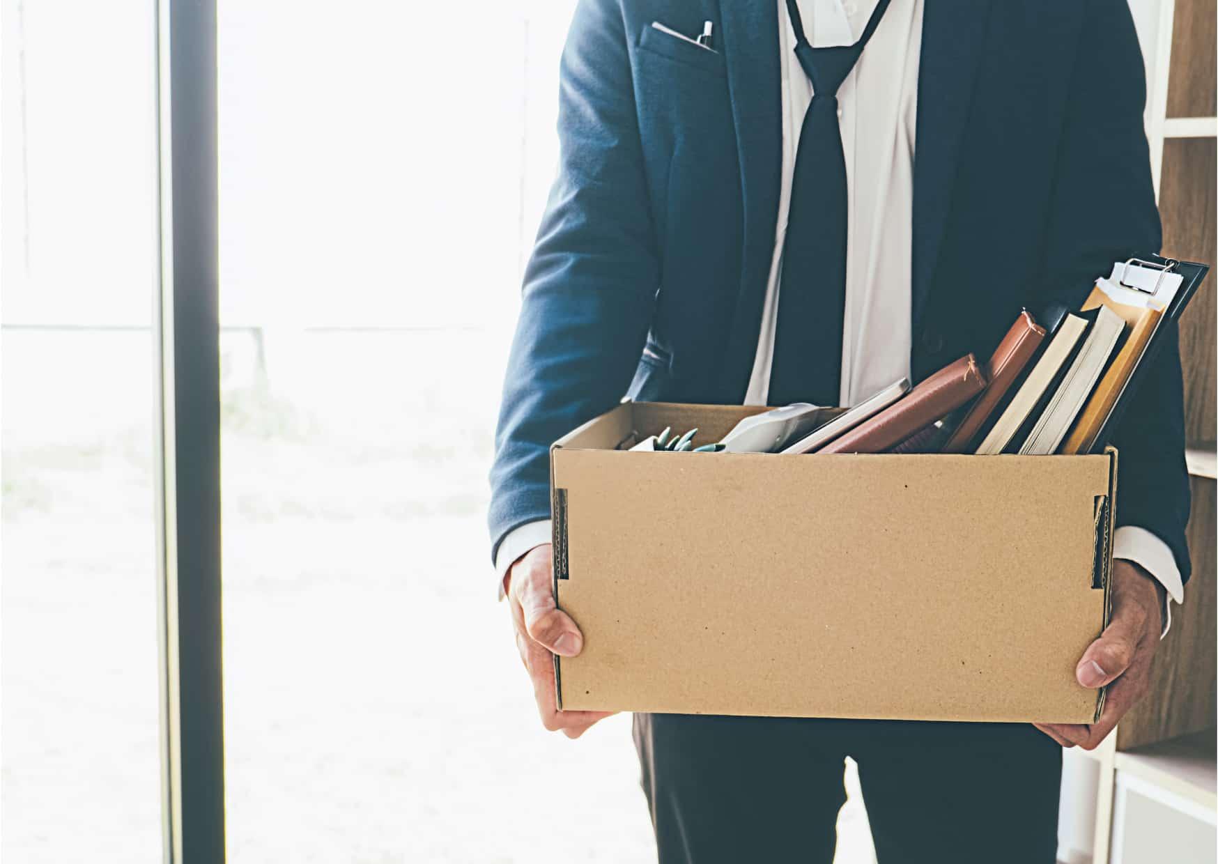 Man met doos met spullen in zijn hand vanwege ontslag